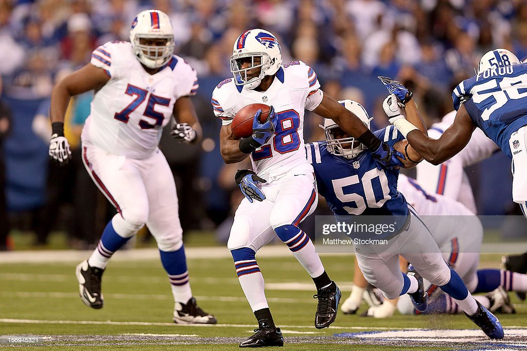 C.J. Spiller #28 of the Buffalo Bills is brought down from behind by Jerrell Freeman #50 of the Indianapolis Colts at Lucas Oil Stadium on November 25, 2012 in Indianapolis, Indiana.