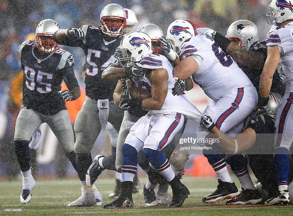 C.J. Spiller #28 of the Buffalo Bills is tackled by members of the New England Patriots in the second half during the game at Gillette Stadium on December 29, 2013 in Foxboro, Massachusetts.