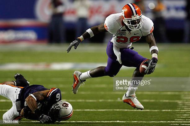J Spiller of the Clemson University Tigers is tripped by Walter McFadden of the Auburn University Tigers during the ChickFilA Bowl on December 31...