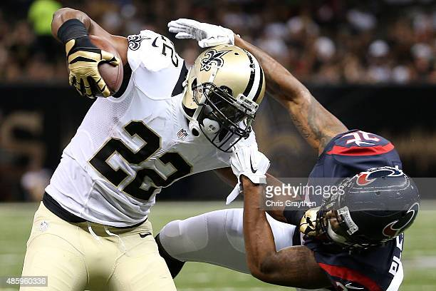 J Spiller of the New Orleans Saints is tackled by Eddie Pleasant of the Houston Texans at the MercedesBenz Superdome on August 30 2015 in New Orleans...