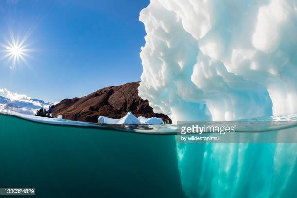 spilt level view of an iceberg in the fjords of eastern greenland. - arctic stock pictures, royalty-free photos & images