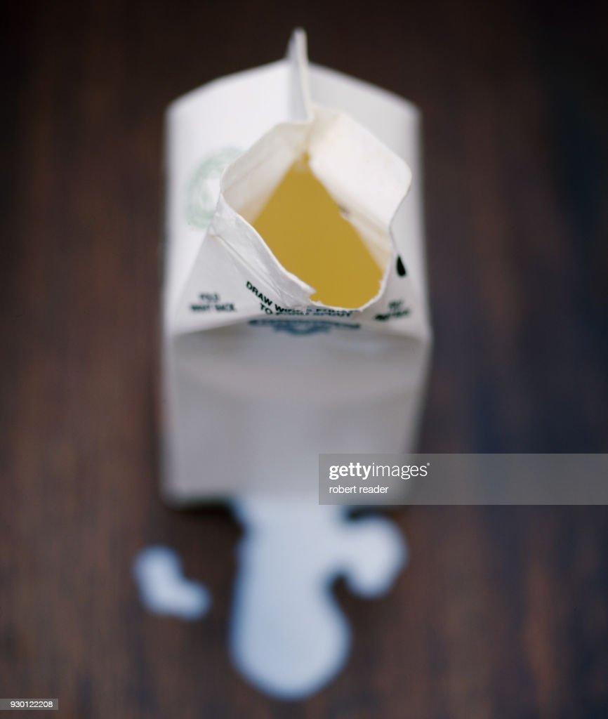 Spilt milk and open carton : Stock Photo