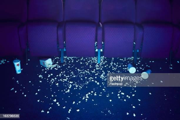 Spilt popcorn and empty drinks on floor of cinema