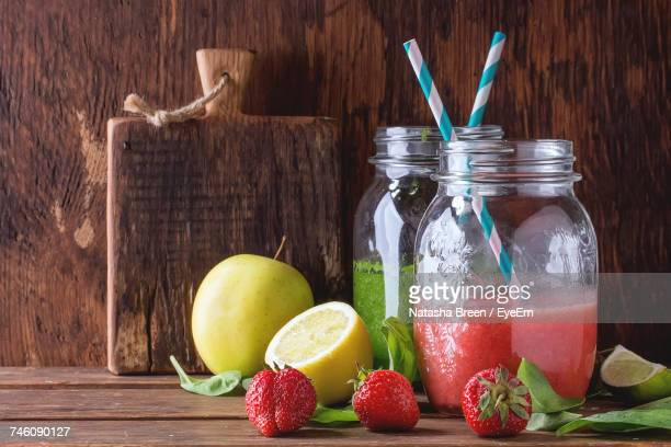 Spinach And Strawberry Smoothie In Jar By Fruits Against Wooden Wall