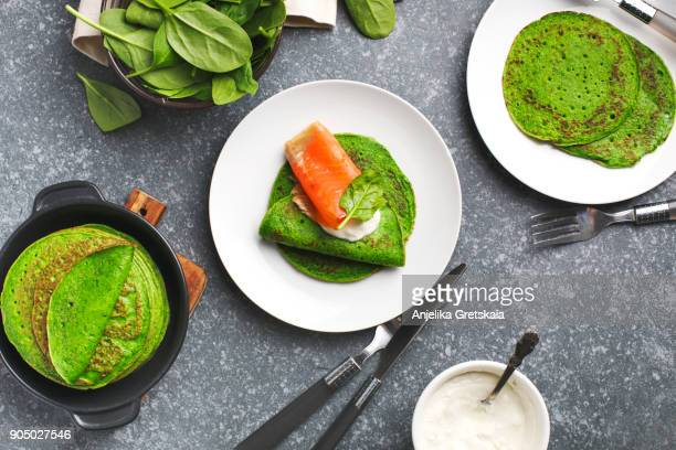 Spinach crepes with smoked salmon and sour cream.