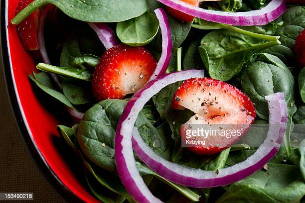 A spinach salad with sliced strawberries and red onions