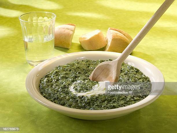 Spinach with sour cream and glass of water with baguette