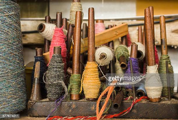spindles of wool in a weaver's workshop - wool stock pictures, royalty-free photos & images