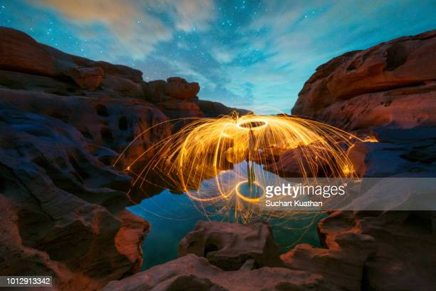 Spinning burning steel wool with water reflection and stars on blue sky at Sam Pan Bok, Grand Canyon of Thailand,