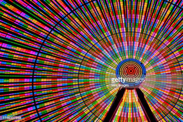 spinning ferris wheel illuminated at night - reuzenrad stockfoto's en -beelden