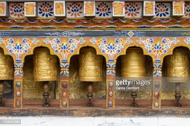 Spinning prayer wheels along temple wall, Bhutan