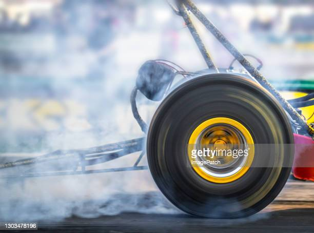 spinning rear wheel of a dragster - sports race stock pictures, royalty-free photos & images