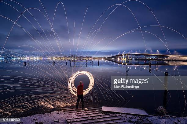 spinning steel wool on the edge of okanagan lake, kelowna, british columbia, canada - kelowna stock pictures, royalty-free photos & images