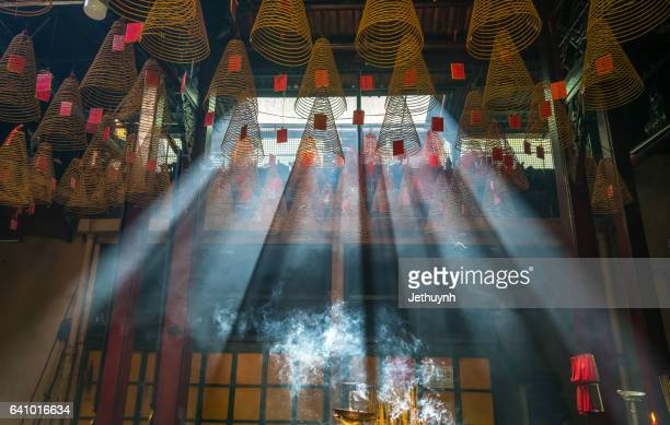 Spiral incense sticks at Thien Hau Temple with smoke and rays