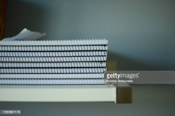 spiral note pads on a white shelf, seen by a blue wall - kristina strasunske stock pictures, royalty-free photos & images