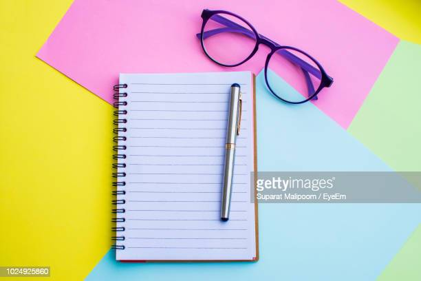 spiral notebook on colorful papers - reading glasses stock pictures, royalty-free photos & images