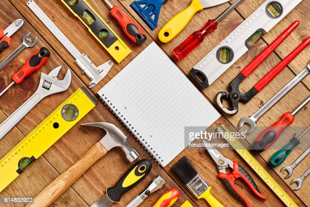 Spiral notebook surrounded by various hand tools on wooden floor