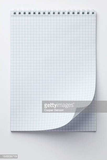 A spiral notepad with graph paper and a curled up page corner