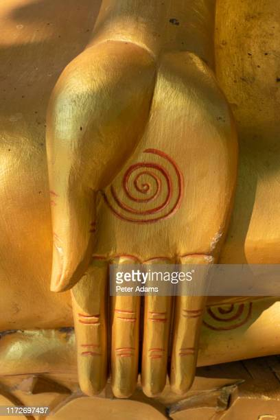 spiral symbol on hand of gold statue of buddha siem reap, cambodia - peter adams stock pictures, royalty-free photos & images