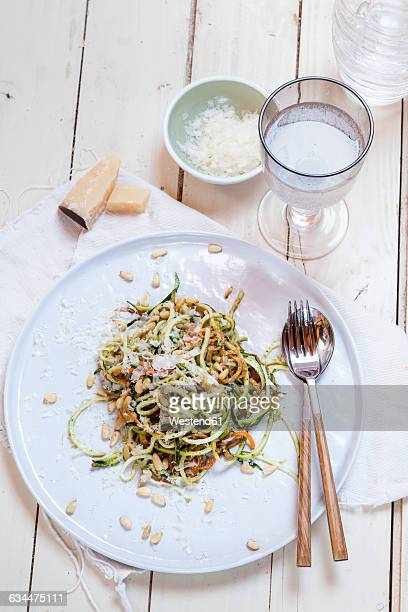 spiralized carrot and zucchini pasta with pesto, parmesan cheese, and pine nuts - marrow squash stock pictures, royalty-free photos & images