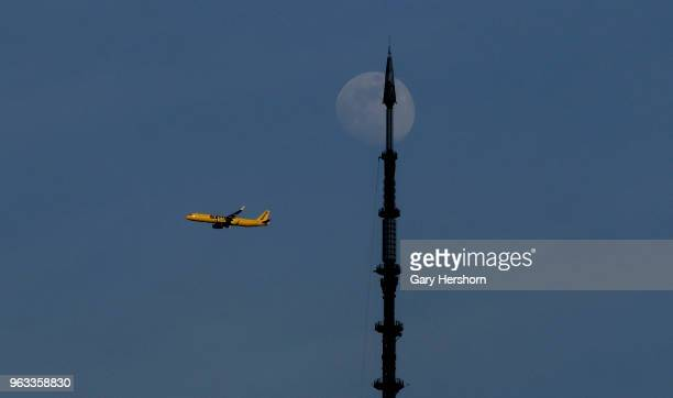 Spirit Airlines airplane flies past the moon and the spire of One World Trade Center in New York City on May 26 2018 as seen from Jersey City New...