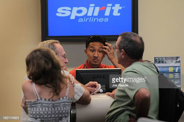 Spirit Airlines Inc employee helps customers at the checkin counter at the Fort Lauderdale International Airport after striking pilots agreed on June...