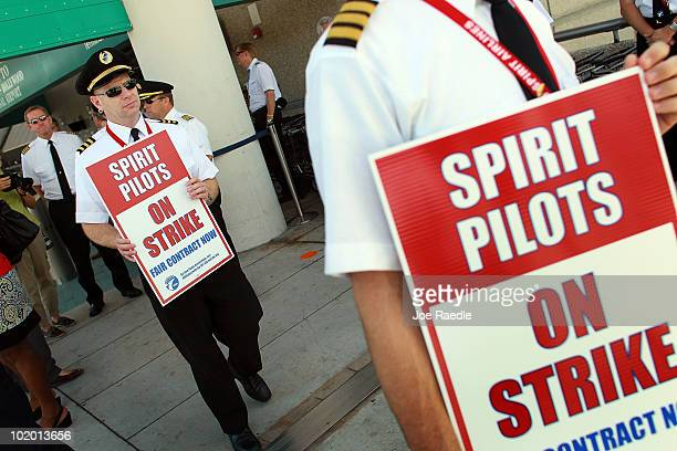 Spirit Airlines Inc pilots hold signs as they picket in front of the terminal at the Fort Lauderdale International Airport after the pilots went on...