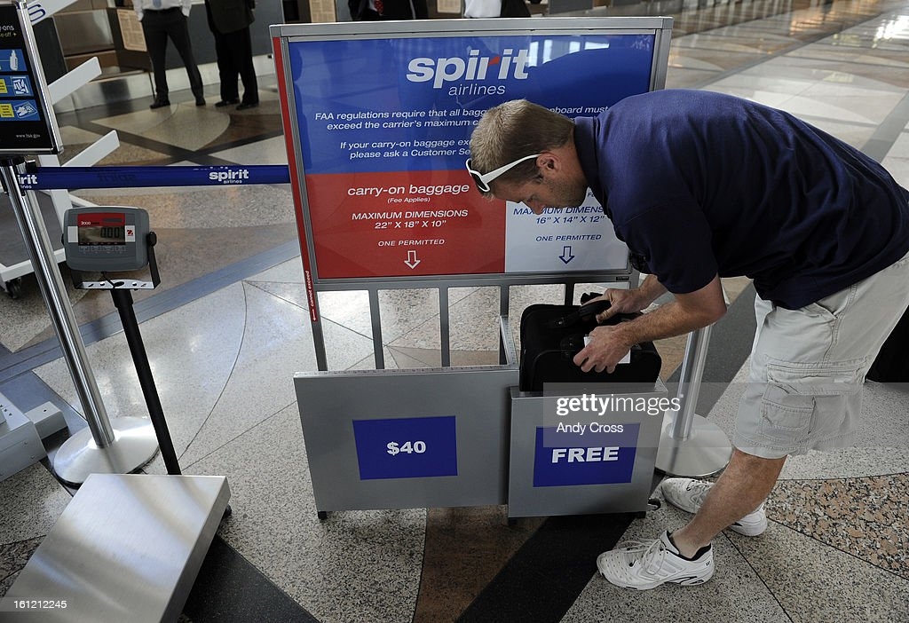 Spirit Airlines passenger, Brian Svigel, stuffs his bag into a template to check to see if it classifies as a 'free' carry-on or if he has to pay $40 before Spirit Airlines first outbound flight to Las Vegas at gate A31 at Denver International Airport Thu : News Photo