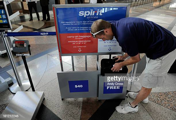 Spirit Airlines passenger Brian Svigel stuffs his bag into a template to check to see if it classifies as a free carryon or if he has to pay $40...