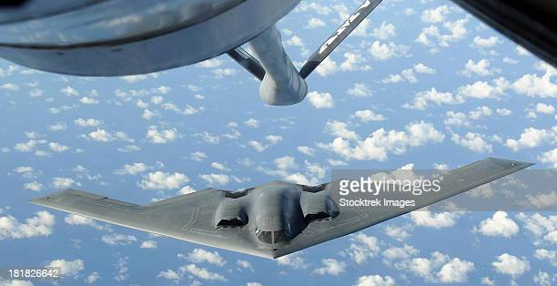 a b-2 spirit approaches the refueling boom of a kc-135 stratotanker. - stealth bomber stock photos and pictures