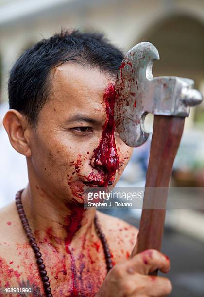 Spirit medium cuts his head during in a street procession at the Phuket Vegetarian Festival in Phuket Town Thailand
