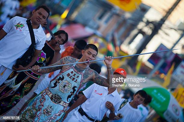 Spirit medium walks in a street procession at the Phuket Vegetarian Festival in Phuket Town Thailand