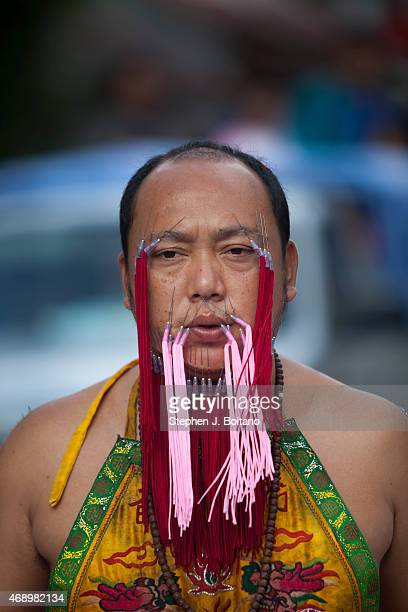 Spirit medium walks in a street procession at the Phuket Vegetarian Festival in Phuket Town Thailand The event is held over a nineday period in...