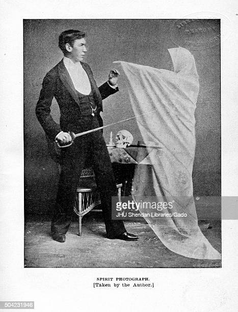 Spirit photograph showing man in formal suit holding a saber and reaching out his hand to touch the hand of a ghost in a white cloak who hovers above...