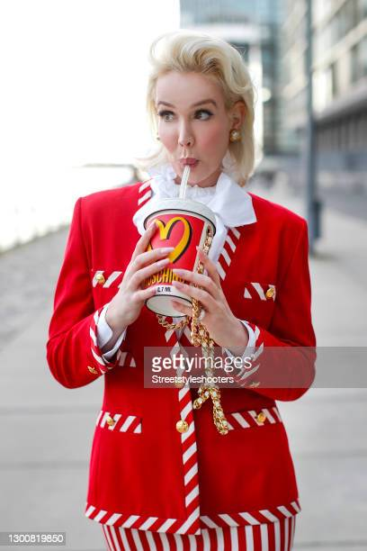Spiritual healer Ira Wolff wearing a red blazer with red and white striped details and gold buttons by Escada, a red, white and yellow milkshake cup...