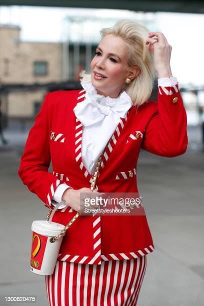 Spiritual healer Ira Wolff wearing a red blazer with red and white striped details and gold buttons by Escada, a red and white striped mini skirt by...