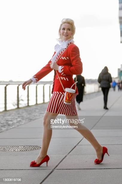 Spiritual healer Ira Wolff wearing vintage red pumps, a red blazer with red and white striped details and gold buttons by Escada, a red and white...