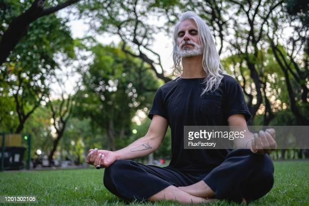 spiritual man in black clothing meditating outdoors - black shirt stock pictures, royalty-free photos & images
