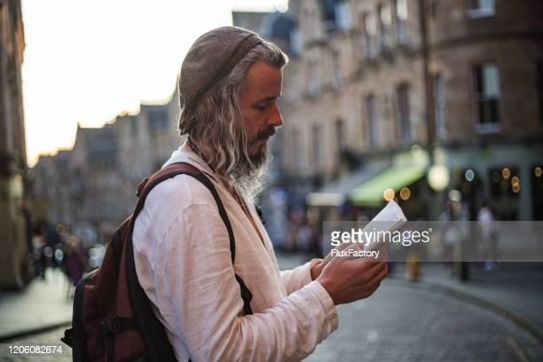 spiritual man reading on a city street - prayer book stock pictures, royalty-free photos & images