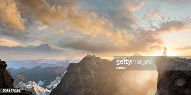 spiritual seeker meditating high on mountain top at sunset - spiritualiteit stockfoto's en -beelden