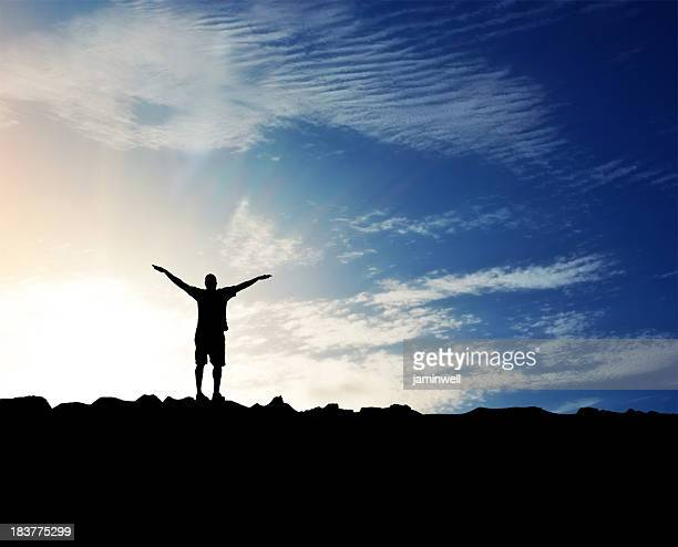 Spirituality; silhouette of man, arms outstretched and glorious sky