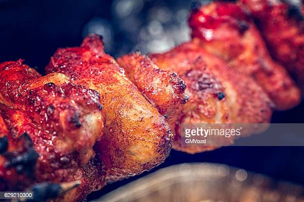Spit Roasted Spicy Chicken Wings on a Barbecue Grill