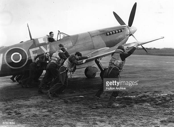 A Battle of Britain type 'scramble' An improved Spitfire is pushed onto the runway by a group of pilots from the squadron