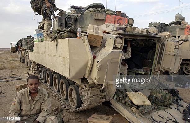 Spl Arthur Wright of New Jersey with Alpha Company 1st Infantry Division sits outside of a Bradley fighting vehicle following the company's battle...