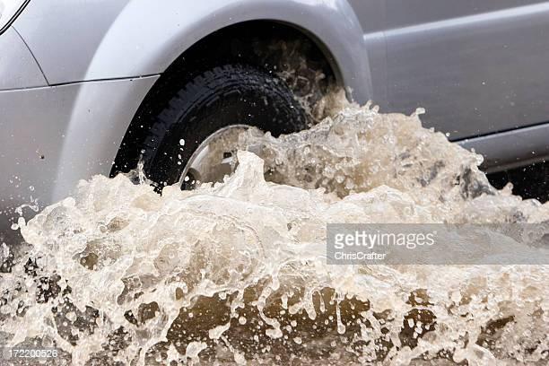 Splash von einem Auto, denn es geht bei Flut Wasser