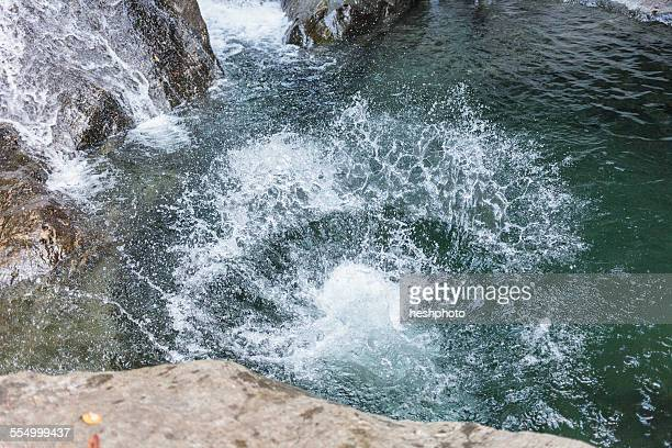 a splash from someone jumping into a swimming hole in the woods with a waterfall - heshphoto stockfoto's en -beelden