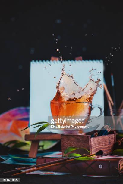 Splash in a tea cup in front of an artist easel with blank canvas. Painting tea time concept with action food photography.