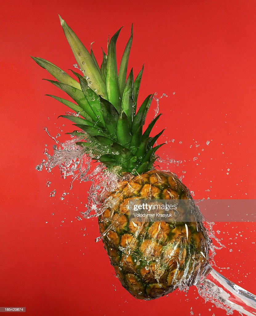 Splash in water with pineapple : Stock Photo
