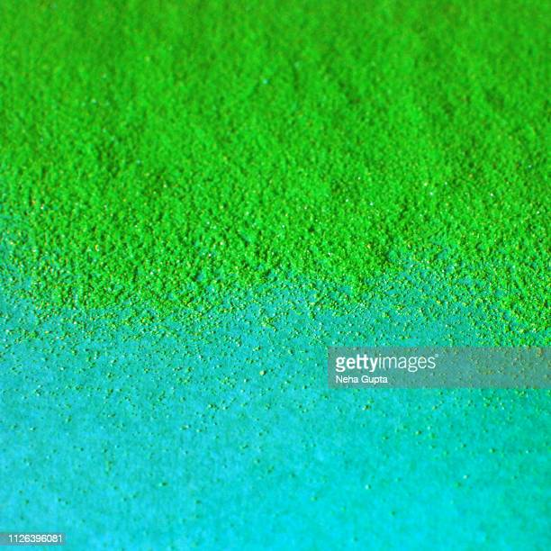 Splash of green powder paint on a turquoise background