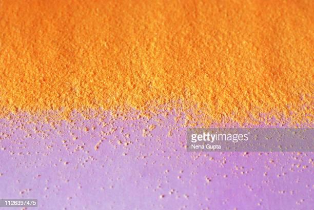 Splash of orange powder paint on a pink background